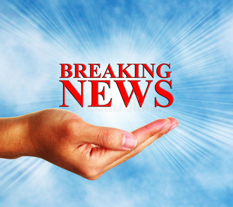 Breaking News. Hand hold the text of Breaking news with blue sky background stock photography