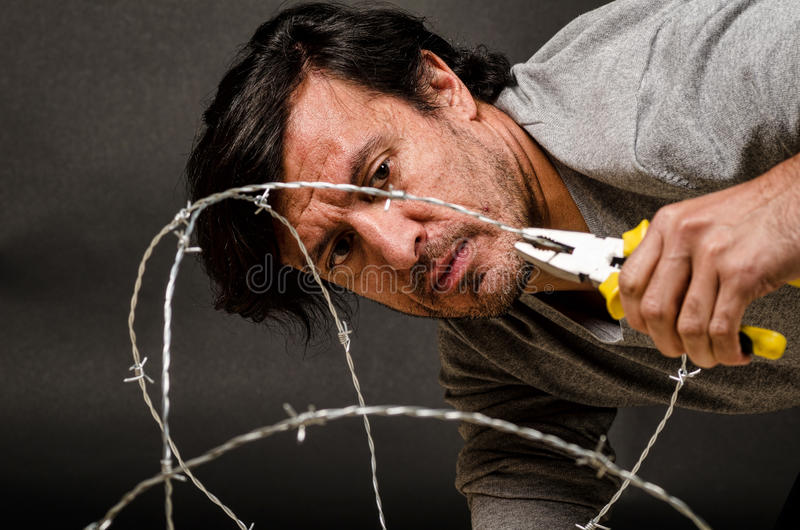 Breaking out. Latino male trying to break through a barbed fence, a conceptual shot royalty free stock photo