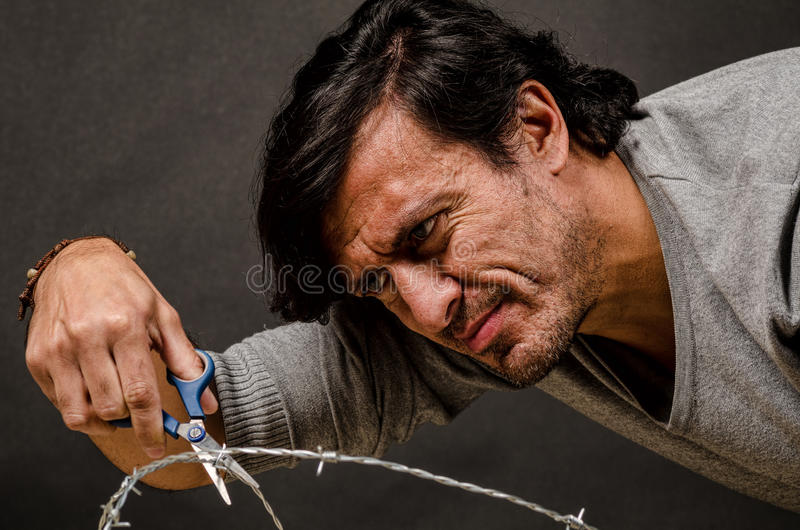 Breaking out. Latino male trying to break through a barbed fence, a conceptual shot royalty free stock photography