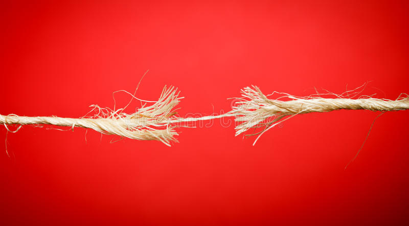 Breaking rope. Frayed rope breaking on red background - suitable as banner image (hanging by a thread stock photography