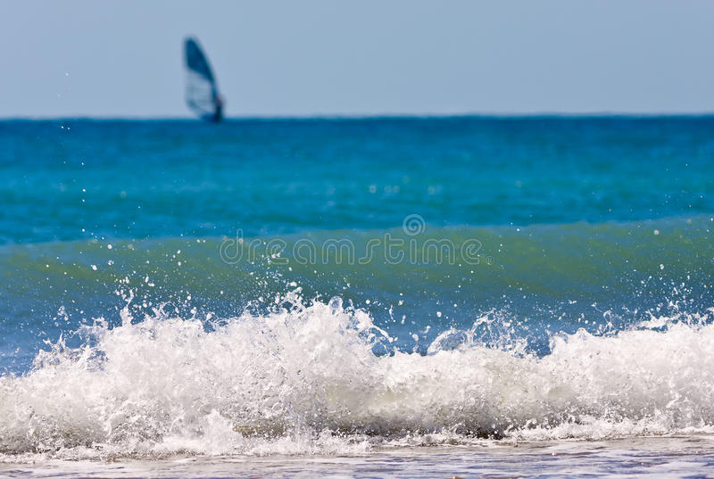 Breaking sea wave with a lone windsurfer on the background scenery royalty free stock photos
