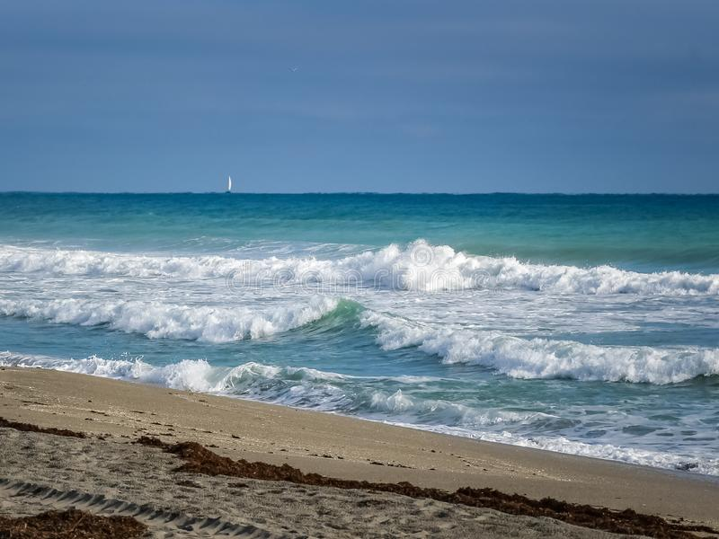 Breaking Waves and a Sailboat stock images
