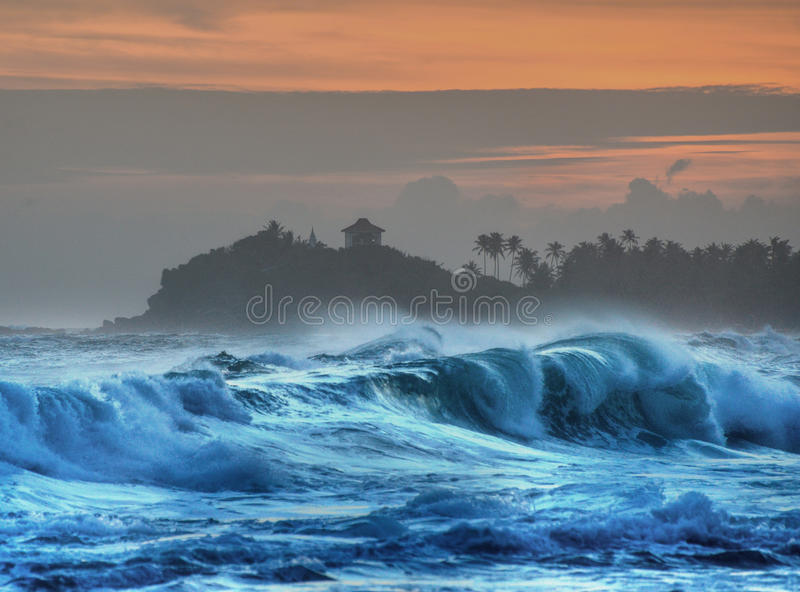 Breaking waves with temple and palm trees in silhouette stock images