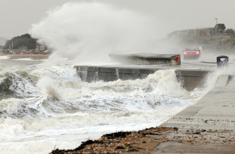 Breaking waves on the waterfront. Waves break over a sea wall and engulf a passing motorist during winter storms stock photo