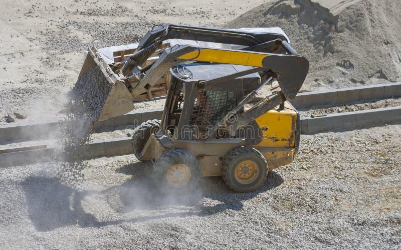 Breakstone movente da escavadora pequena do carregador na área da construção fotografia de stock