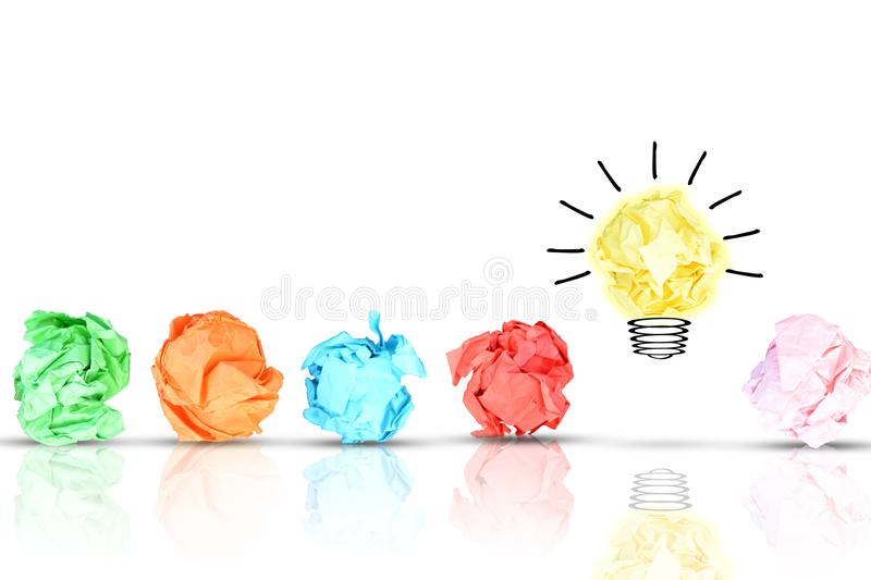 Breakthrough concept with multiple colorful crumpled pieces of paper around a yellow bright light bulb shaped paper on white backg royalty free stock image