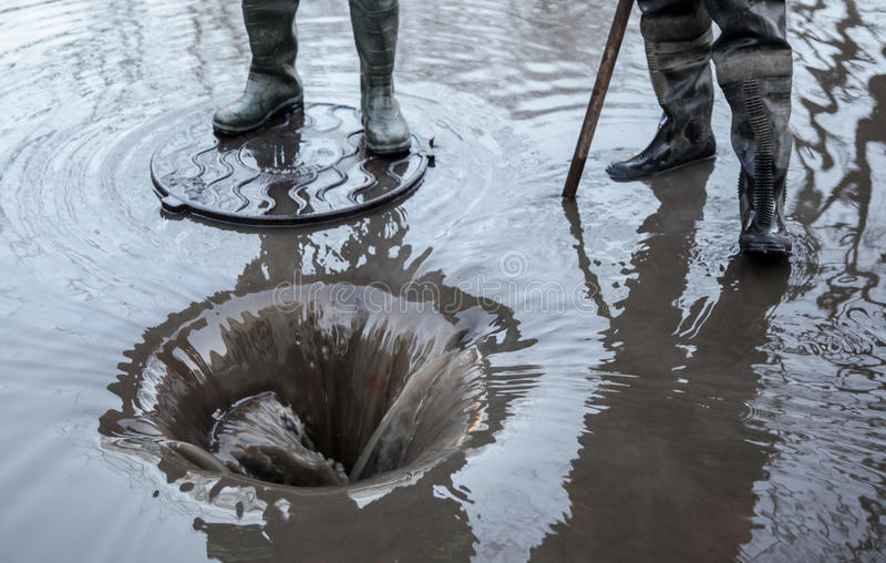 Breakthrough on a heating pipe. Workers in Boots drained water. royalty free stock photo