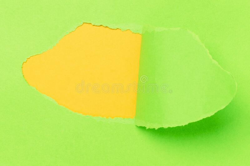 Breakthrough paper hole with a yellow background stock photo