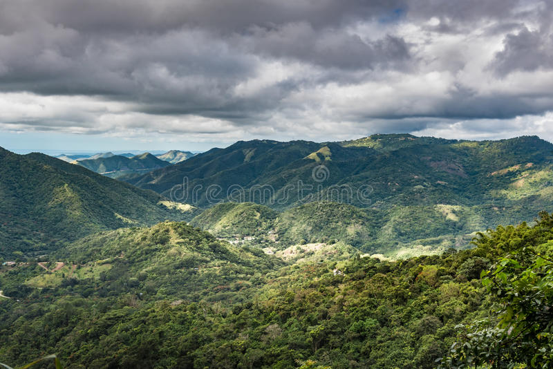Breakthrough sun on the valley between the tropical mountains stock image