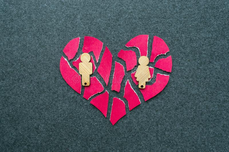 Breakup, divorce, failed relationship concept. Broken, mosaic, p. Ieces pink heart with wooden figures of man and woman on a gray background stock photography