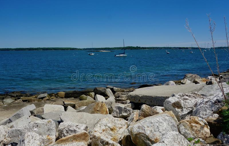 Breakwater along Casco Bay, Portland, Maine rocks stones. Protection safety guard harbor coastal rubble ships on the bay summer day royalty free stock images
