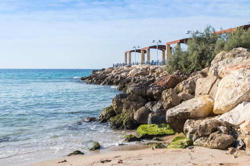 Breakwater overlooking the sea with a promenade terrace on the waterfront of Nahariya city in Israel stock photos