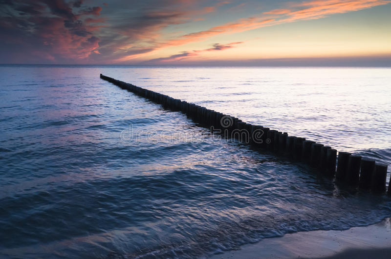 Breakwater in sea. Wooden breakwater receding in sea with sunset background stock photos