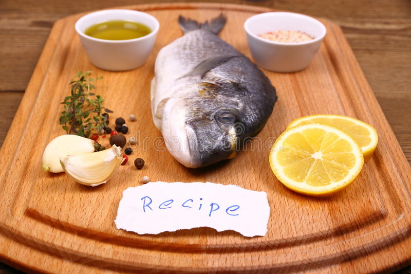 Bream fish on cutting board, recipe label stock images