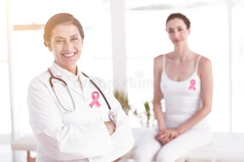Composite image of breast cancer awareness ribbon. Breast cancer awareness ribbon against doctor and patient smiling at camera stock images
