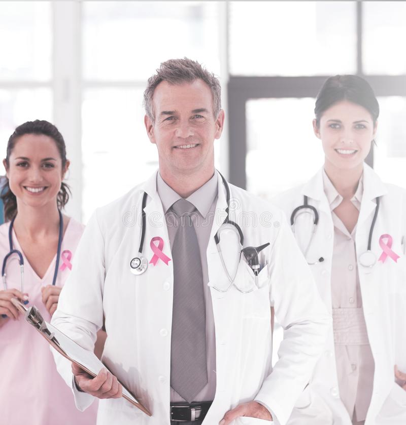 Composite image of breast cancer awareness ribbon. Breast cancer awareness ribbon against portrait of senior smiling doctor with his colleagues stock photography