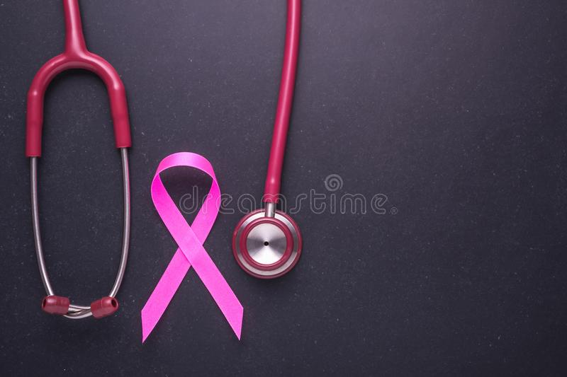 Breast Cancer concept : Pink ribbon symbol of breast cancer and. Doctor Stethoscope on black stone board background stock photo