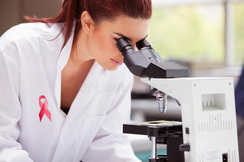 Composite image of breast cancer ribbon. Breast cancer ribbon against scientist looking into a microscope royalty free stock photo