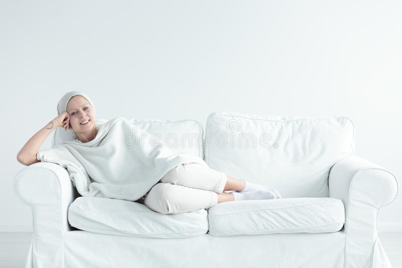Breast cancer survivor on couch. Breast cancer survivor lying on a couch smiling happily stock photos