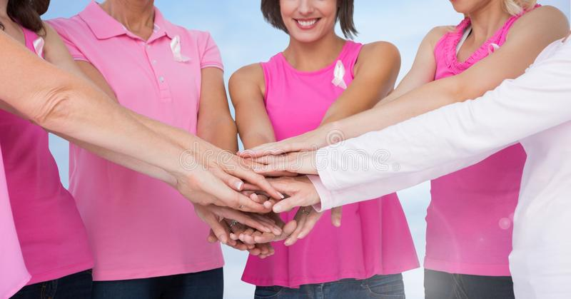 Breast cancer women holding hands with sky clouds background. Digital composite of Breast cancer women holding hands with sky clouds background stock photos