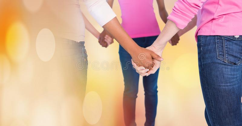 Breast cancer women with transition holding hands. Digital composite of Breast cancer women with transition holding hands royalty free stock photography