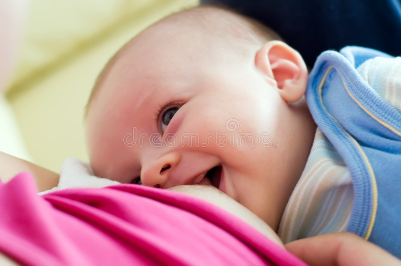 Breast feeding fun. Mother breast feeding her newborn. Baby is smiling and having a look at mother royalty free stock image