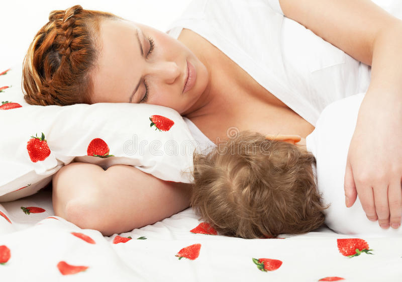 Breast feeding. Mother breast feeding her child on the bed stock images