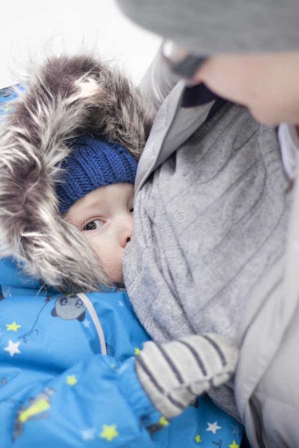 Breast-feeding in unusual circumstance. Mother feed baby outside. In cold winter weather. Boy suckles despite on weather, happy and calm royalty free stock photo