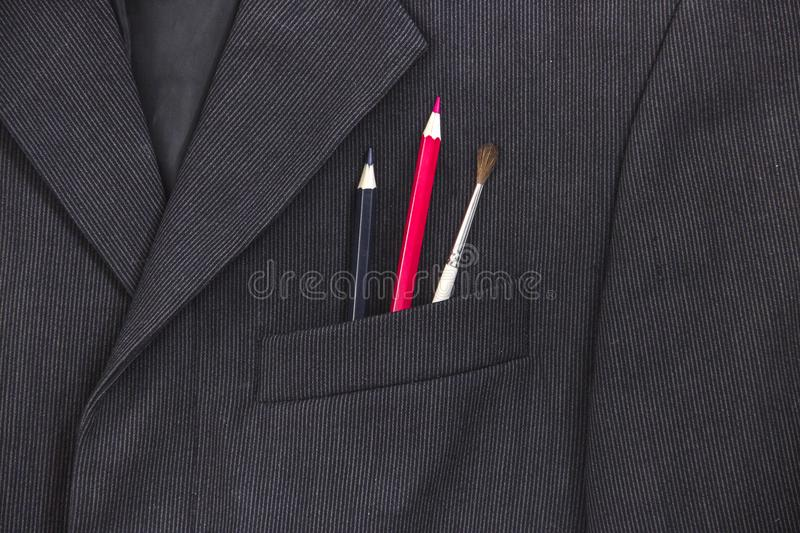 In the breast pocket of a dark black man`s jacket a pencil and a brush lay in a light strip red blue stock image