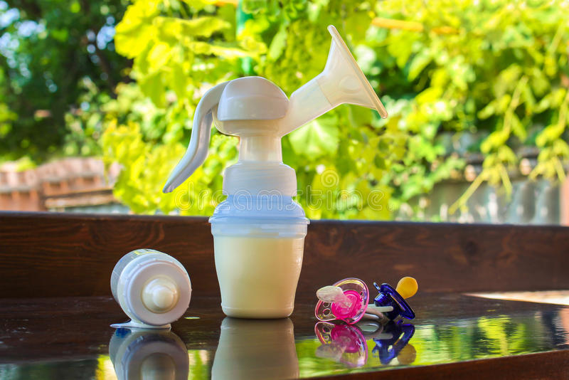 Breast pump, bottle of milk and pacifiers. On the table royalty free stock image