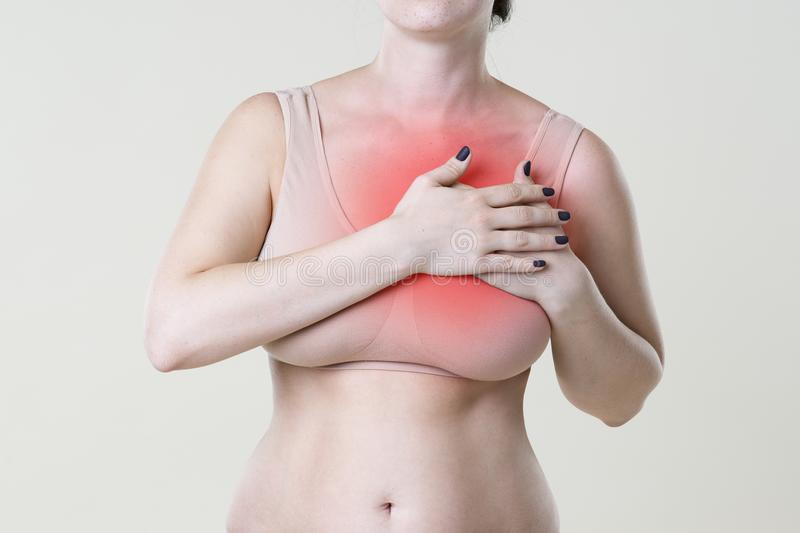 Breast test, woman examining her breasts for cancer, heart attack, pain in human body. On beige background stock image