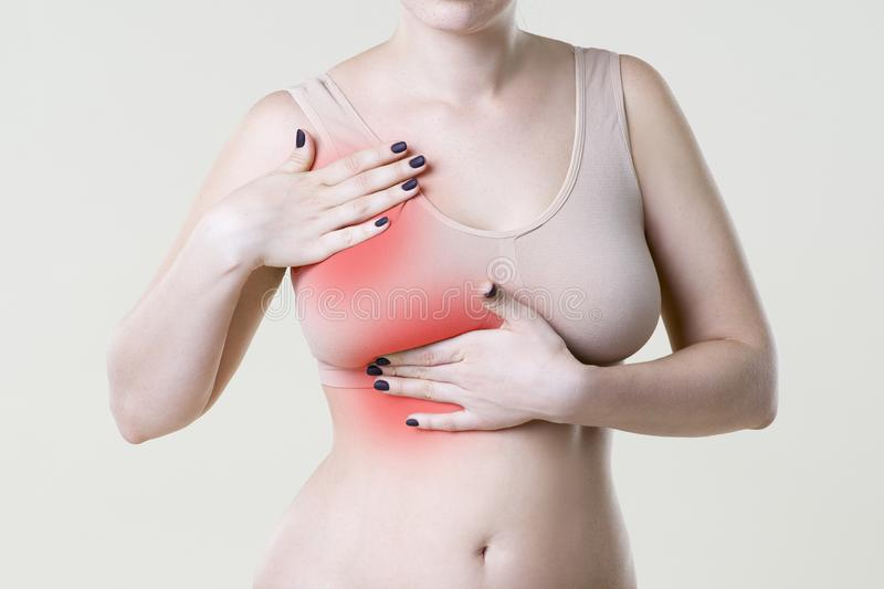 Breast test, woman examining her breasts for cancer, heart attack, pain in human body. On beige background stock photos