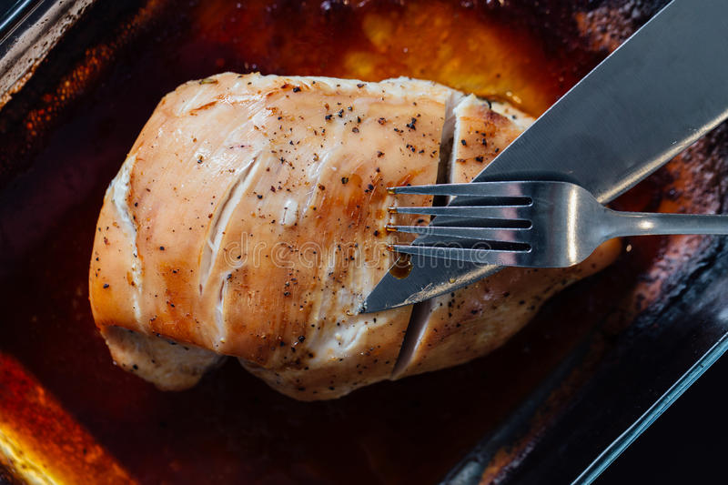 Breast of turkey with spices, rosemary in soy sauce. There is a knife and fork, the first cut. Breast of turkey with spices, rosemary in soy sauce. There is a royalty free stock photo