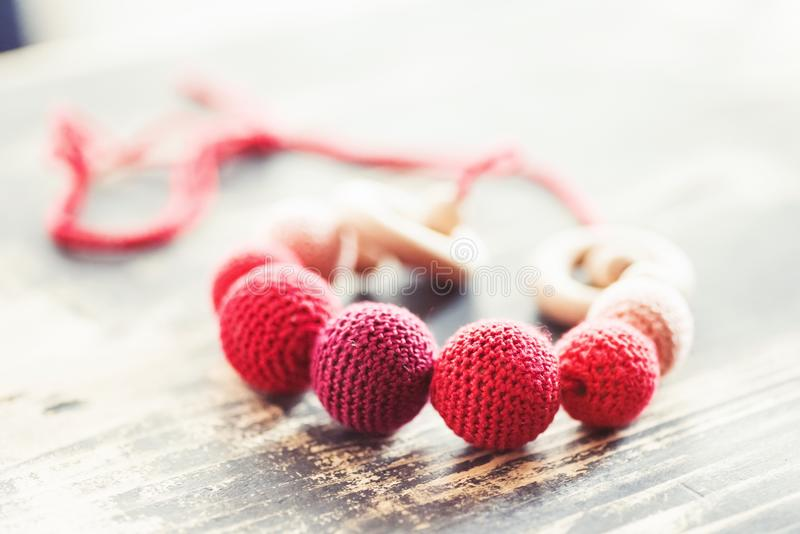 Breastfeeding beads. Sling beads made of wood and dressed in red crocheted organic cotton stock photos