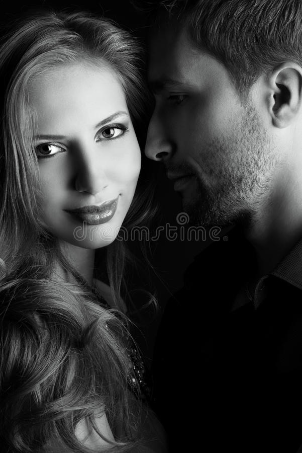 Breath of love. Portrait of a beautiful young couple in love posing at studio over dark background stock image