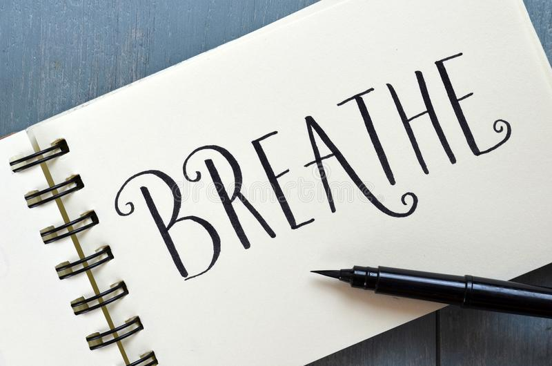 BREATHE hand-lettered in notepad with brush pen stock image