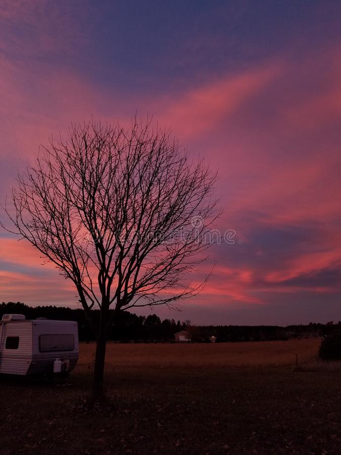 Breathless. Another One of my favorite sunset pictures with an old camper and tree stock photo