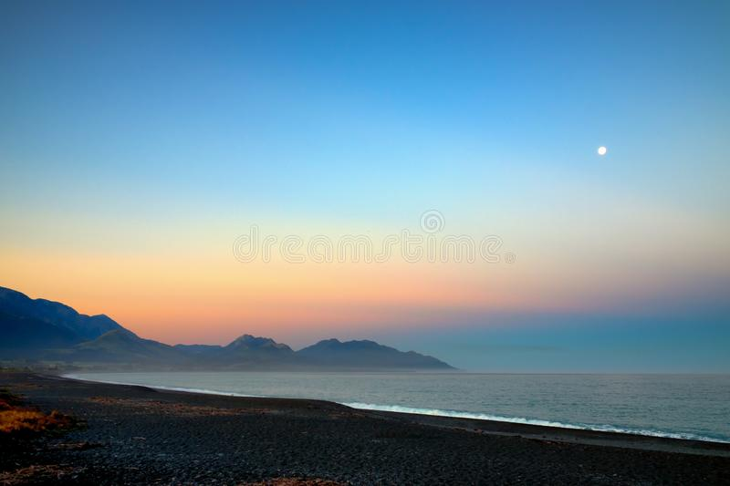 A breathtaking beach. This was taken in Kaikoura, New Zealand. It was early morning and the rising sun shines a golden orange stock image