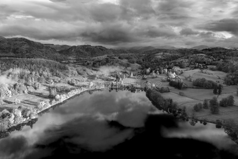 Breathtaking black and white aerial drone landscape images over Coniston Water at sunrise on beautiful Autumn Fall morning stock images