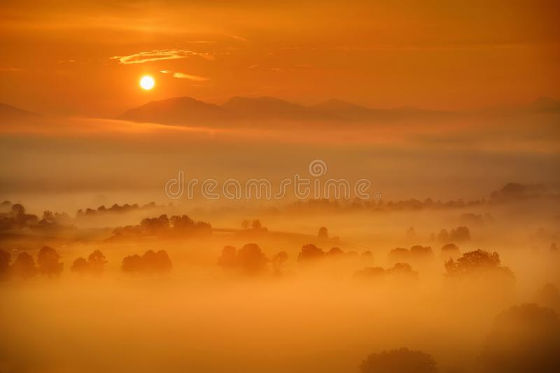 Breathtaking morning lansdcape of small bavarian village covered in fog. Scenic view of Bavarian Alps at sunrise with majestic mou royalty free stock photos