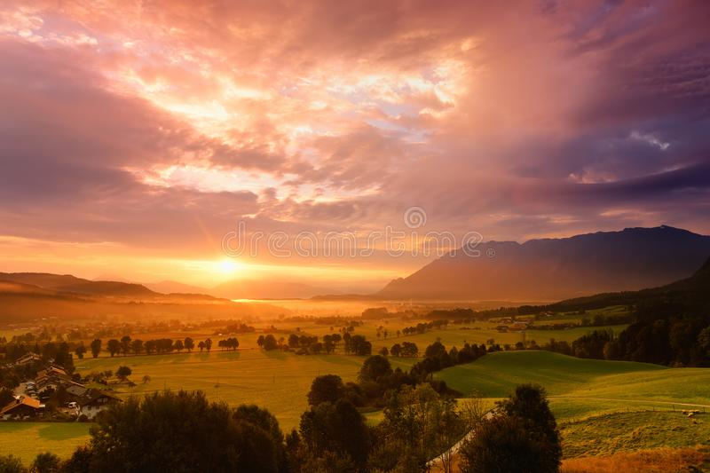 Breathtaking morning lansdcape of small bavarian village covered in fog. Scenic view of Bavarian Alps at sunrise with majestic mou stock photo