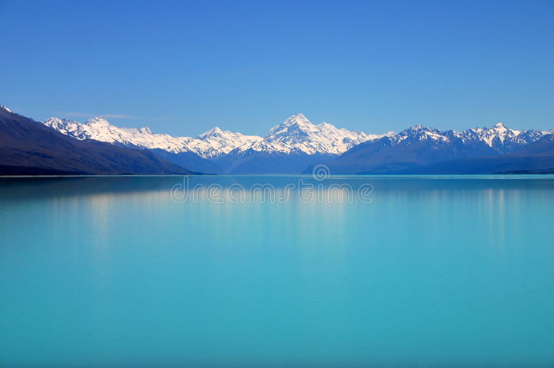 Breathtaking mountain lake. Beautiful mountain turquoise color lake, blue sky and snow peaks reflecting in the water. Untouched nature. Mount Cook National Park stock photos