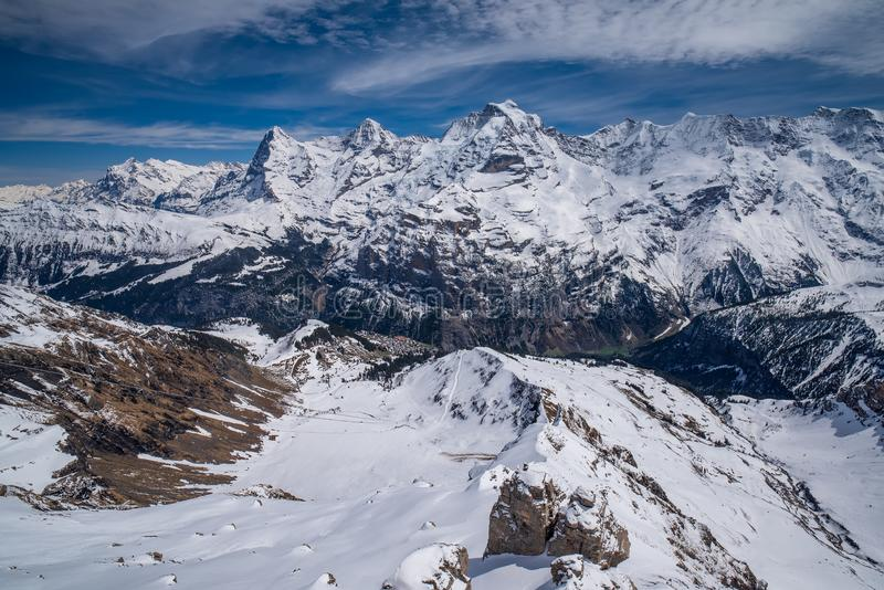 Breathtaking panoramic view of famous peaks Eiger, Monch and Jungfrau in Swiss Alps, Switzerland. Breathtaking panoramic view of snow capped Swiss Alps with stock images