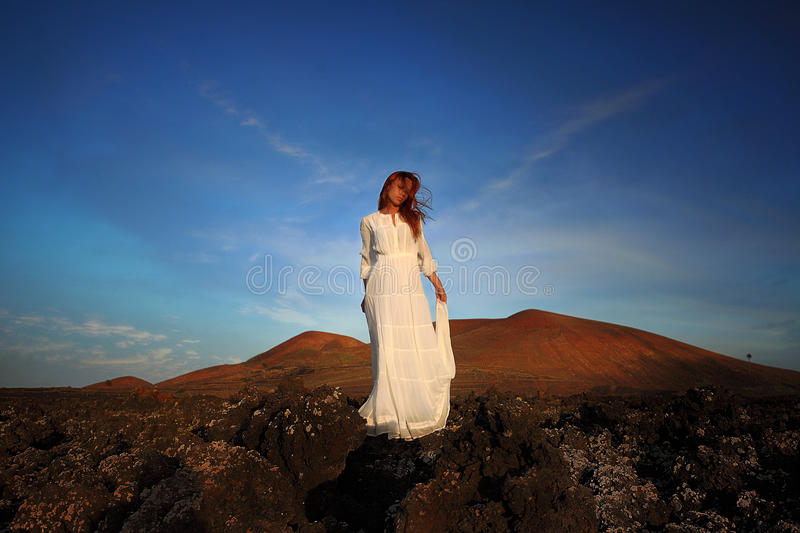 Breathtaking portrait of redhead woman in white dress standing on the hill. breathink with closed eyes. Lanzarote, Canary Islands, stock images