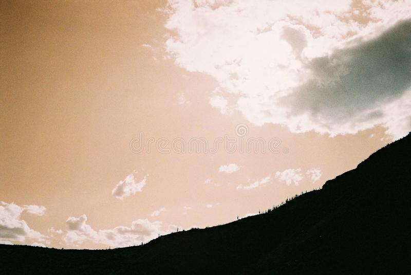 Breathtaking silhouette of a beautiful mountain range under the colorful cloudy sky. A breathtaking silhouette of a beautiful mountain range under the colorful royalty free stock image