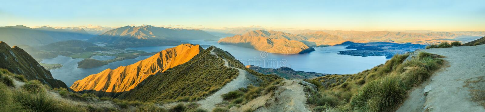 Breathtaking, Stunning Panoramic Landscape View from Roys Peak on Lake Wanaka with golden sunshine light at twilight, South Island royalty free stock images