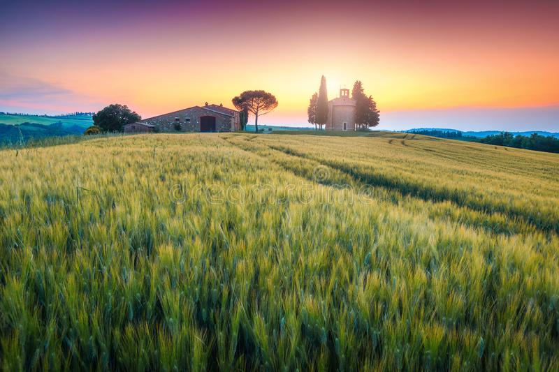 Fantastic Vitaleta chapel at sunset, near Pienza, Tuscany, Italy, Europe. Breathtaking Tuscany landscape, cute Vitaleta chapel Capella di Vitaleta with farmland stock photos