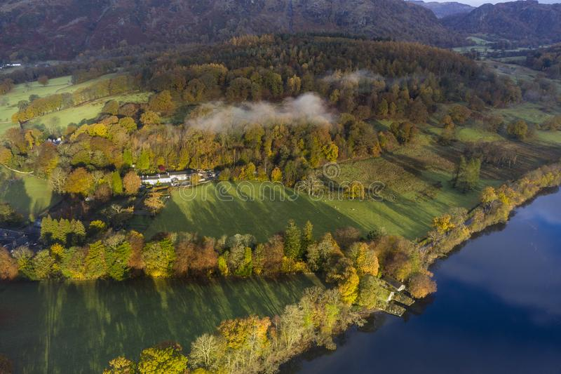 Breathtaking vibrant aerial drone landscape images over Coniston Water at sunrise on beautiful Autumn Fall morning royalty free stock image