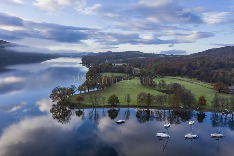Breathtaking vibrant aerial drone landscape images over Coniston Water at sunrise on beautiful Autumn Fall morning stock photo
