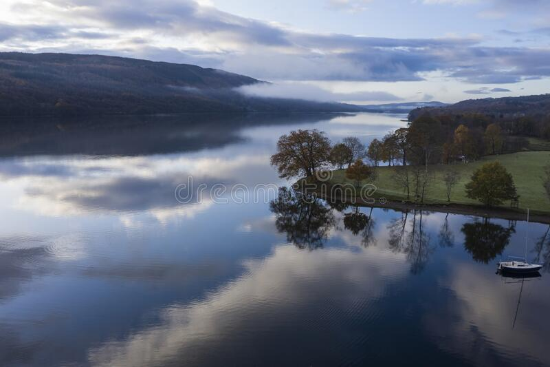 Breathtaking vibrant aerial drone landscape images over Coniston Water at sunrise on beautiful Autumn Fall morning stock images